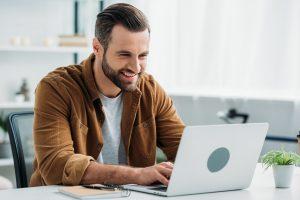 Man sitzt lächelnd vor dem PC und hat Erfolg beim Online Dating